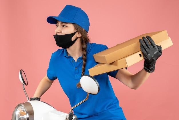 Halve lichaamsopname van een jonge nieuwsgierige vrouwelijke koerier met een medisch masker en handschoenen die op een scooter zitten met dozen op een pastelkleurige perzikachtergrond