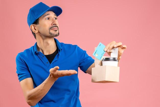 Halve lichaamsopname van een nieuwsgierige mannelijke bezorger met een hoed met bestellingen en een bankkaart