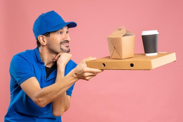 Halve lichaamsopname van een positieve, tevreden mannelijke bezorger met een hoed die bestellingen vasthoudt