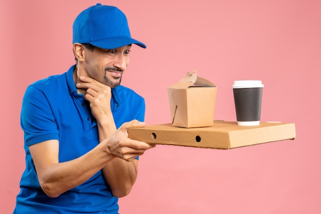 Halve lichaamsopname van een tevreden mannelijke bezorger met een hoed die bestellingen vasthoudt op een pastelkleurige perzikachtergrond