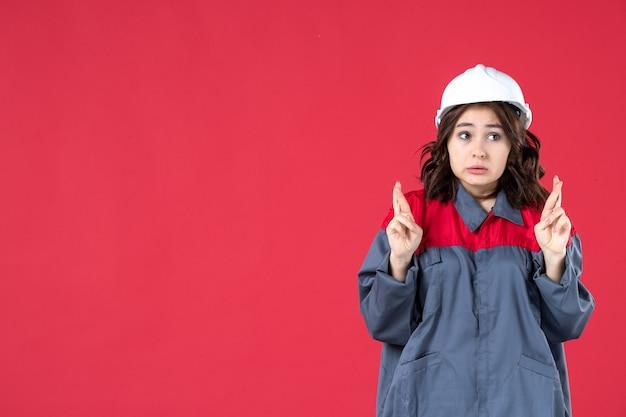 Halve lichaamsopname van een verraste vrouwelijke bouwer in uniform met een helm en haar vingers kruisend op een geïsoleerde rode achtergrond
