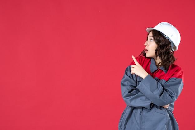Halve lichaamsopname van een verraste vrouwelijke bouwer in uniform met harde hoed en naar boven gericht aan de rechterkant op geïsoleerde rode achtergrond