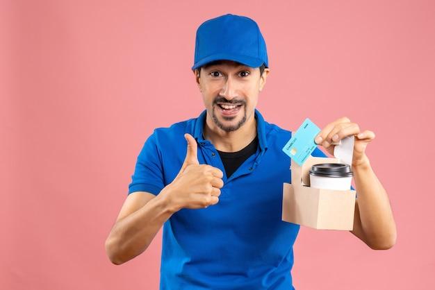 Halve lichaamsopname van een zelfverzekerde mannelijke bezorger met een hoed die bestellingen vasthoudt en een bankkaart die een goed gebaar maakt
