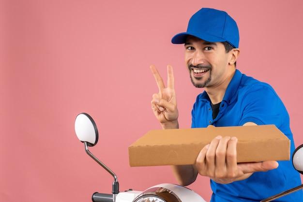 Halve lichaamsopname van een zelfverzekerde mannelijke bezorger met een hoed die op een scooter zit en de bestelling vasthoudt en een overwinningsgebaar maakt