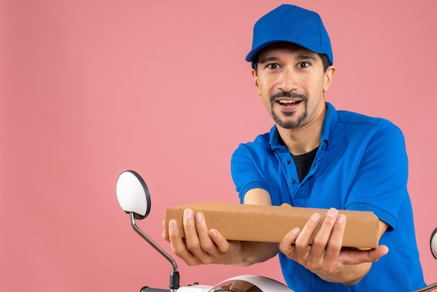 Halve lichaamsopname van een zelfverzekerde mannelijke bezorger met een hoed die op een scooter zit en de bestelling vasthoudt