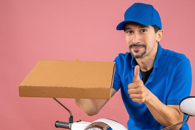 Halve lichaamsopname van een zelfverzekerde mannelijke bezorger met een hoed die op een scooter zit en een bestelling vasthoudt en een goed gebaar maakt