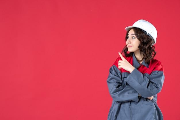 Halve lichaamsopname van lachende, gefocuste vrouwelijke bouwer in uniform met helm en omhoog gericht aan de rechterkant op geïsoleerde rode achtergrond