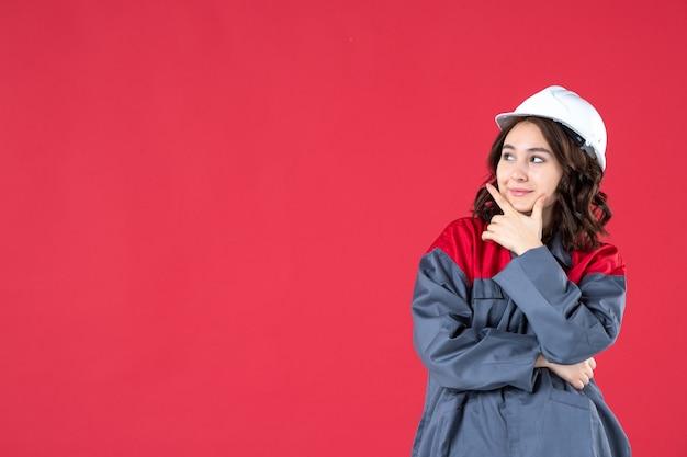 Halve lichaamsopname van lachende vrouwelijke bouwer in uniform met helm en geconcentreerd op iets op geïsoleerde rode achtergrond