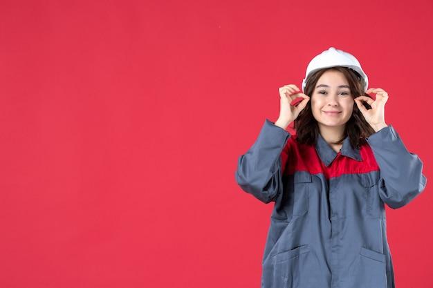 Halve lichaamsopname van lachende vrouwelijke bouwer in uniform met helm op geïsoleerde rode achtergrond