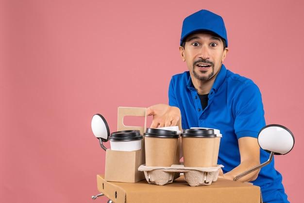 Halve lichaamsopname van mannelijke bezorger met masker met hoed op scooter die bestellingen aflevert