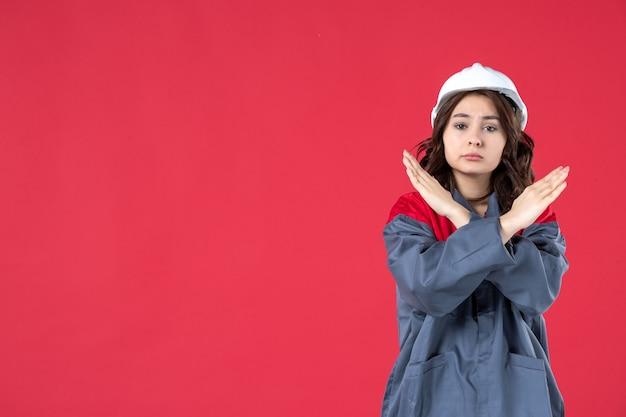 Halve lichaamsopname van nerveuze vrouwelijke bouwer in uniform met harde hoed en stopgebaar maken op geïsoleerde rode achtergrond