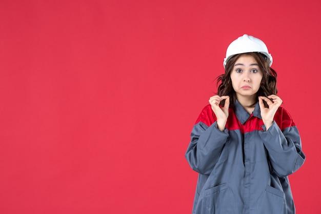 Halve lichaamsopname van ongelukkige vrouwelijke bouwer in uniform met helm op geïsoleerde rode achtergrond