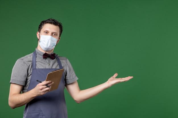 Halve lichaamsopname van zelfverzekerde kerelserver in uniform met medisch masker en met een chequeboekpen die iets aan de linkerkant op een groene achtergrond wijst