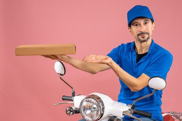 Halve lichaamsopname van zelfverzekerde mannelijke bezorger die een hoed draagt terwijl hij op de openingsopdracht van de scooter zit