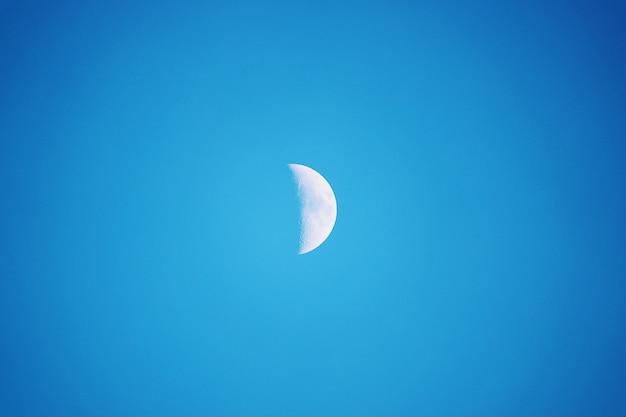 Halve maan gezien overdag, in een blauwe hemel