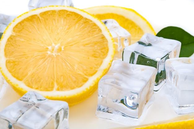 Halve sappige heldere citroen en verfrissende ijsblokjesclose-up