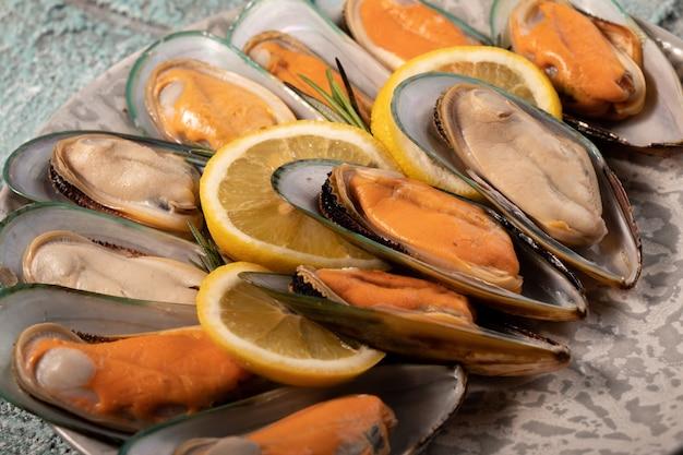 Halve schelpen met mosselvlees en citroen close-up