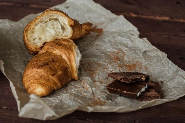 Halve twee van een croissant en een koffie op een zwarte houten lijst sluiten omhoog