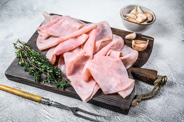 Ham dun gesneden op houten snijplank met kruiden.