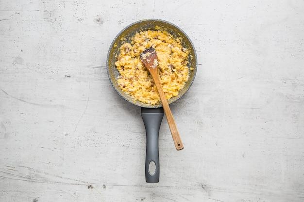 Ham en eieren. roerei met spek in keramische pan.