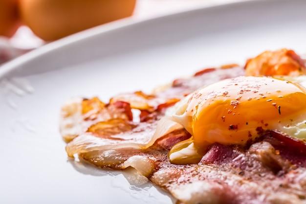 Ham en eieren. spek en eieren. gezouten ei en bestrooid met rode peper. engels ontbijt.