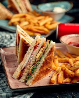Ham en omelet club sandwich en aardappelen