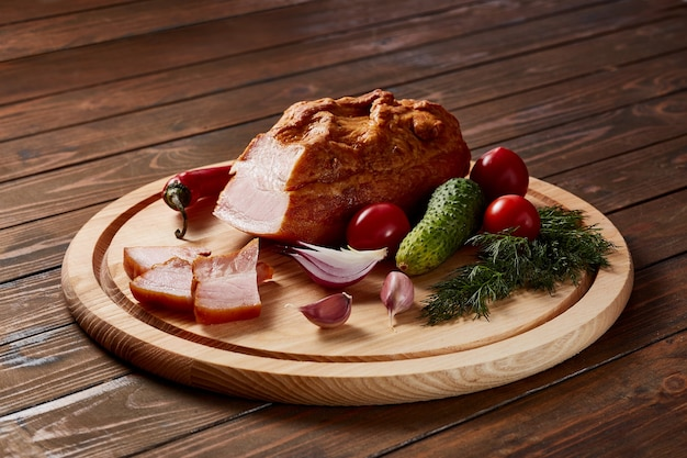Ham gegarneerd met groenten, fruit en kruiden met sauzen en brood op een houten plaat op een donkere houten tafel.