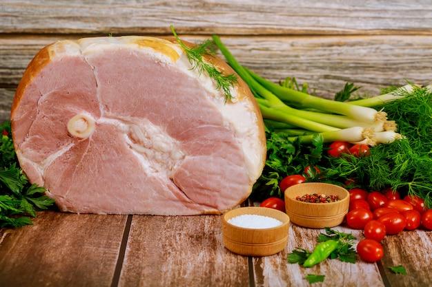 Ham met verse dille, bieslook en tomaat op houten tafel