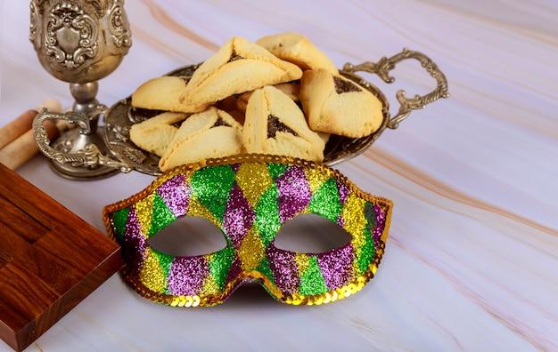 Hamans oren koekjes noisemaker en masker voor purim viering joodse vakantie carnaval en koosjer wijn