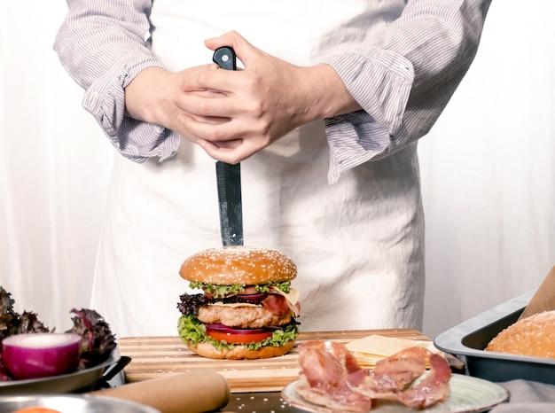 Hamburger cheeseburger hamburger grote chif kok koken witte achtergrond huis