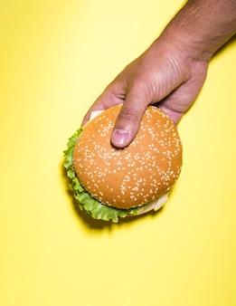 Hamburger die over gele achtergrond wordt gehouden