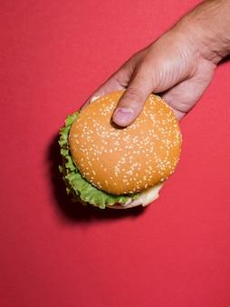 Hamburger die over rode achtergrond wordt gehouden