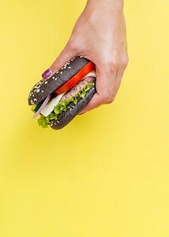 Hamburger die voor gele achtergrond wordt gehouden