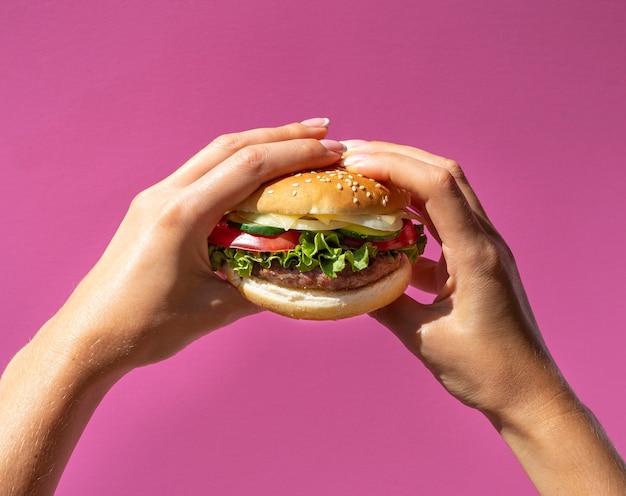 Hamburger die voor purpere achtergrond wordt gehouden