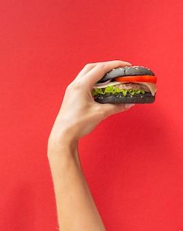 Hamburger die voor rode achtergrond wordt gehouden