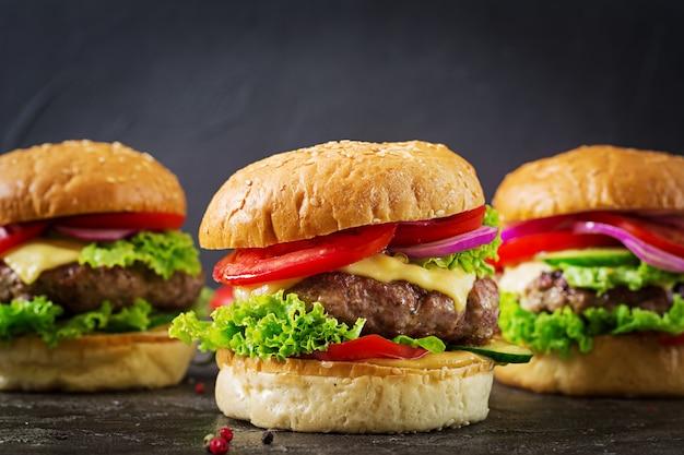 Hamburger drie met de hamburger van het rundvleesvlees en verse groenten op donkere achtergrond.