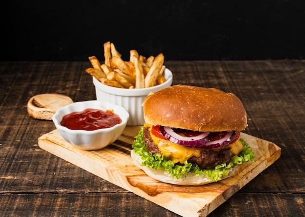 Hamburger en friet op snijplank