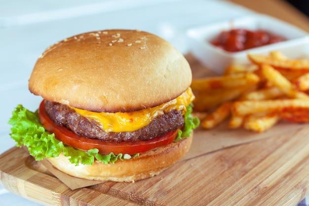 Hamburger en frieten op houten lijst