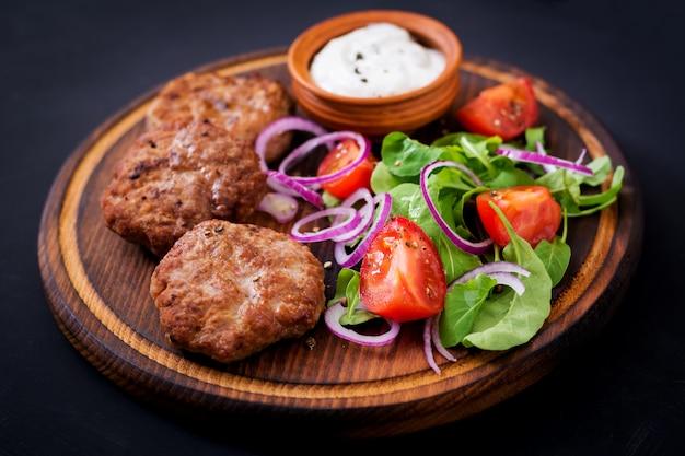 Hamburger en tomaat met basilicum en kruiden op een bruine plaat