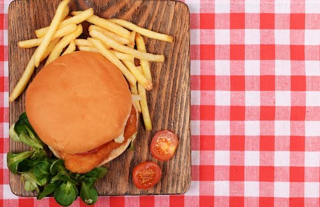 Hamburger, franse frietjes en tomaat op tafelblad bekijken