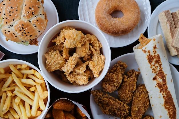 Hamburger, friet, donut, goudklompjes en chocolade op zwart