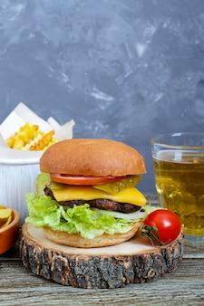 Hamburger, frietjes, chips, drinken op een houten achtergrond. straatvoedsel. set van fastfoodproducten.
