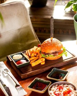 Hamburger geserveerd met frietjes, ketchup en mayonaise