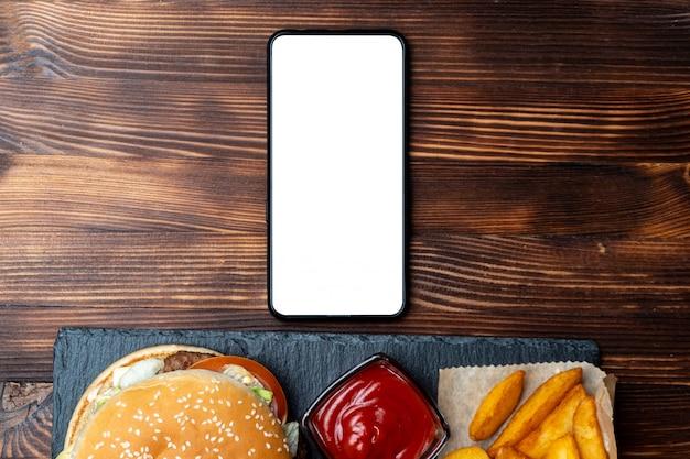Hamburger in papier met met aardappelen in een rustieke en ketchup en op leisteen, zwarte bord en verbrand hout achtergrond met smartphone