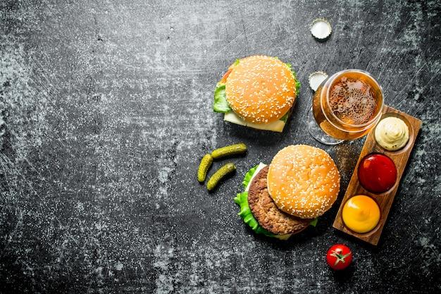 Hamburger met bier, sauzen en augurken op zwarte houten tafel