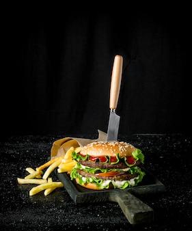 Hamburger met een mes en frietjes. op rustieke achtergrond