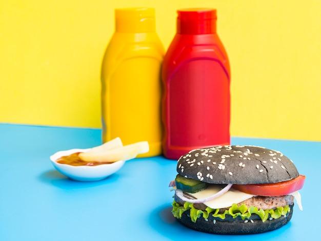 Hamburger met erachter ketchup en mosterd