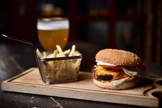 Hamburger met frietjes en bier op een houten bord