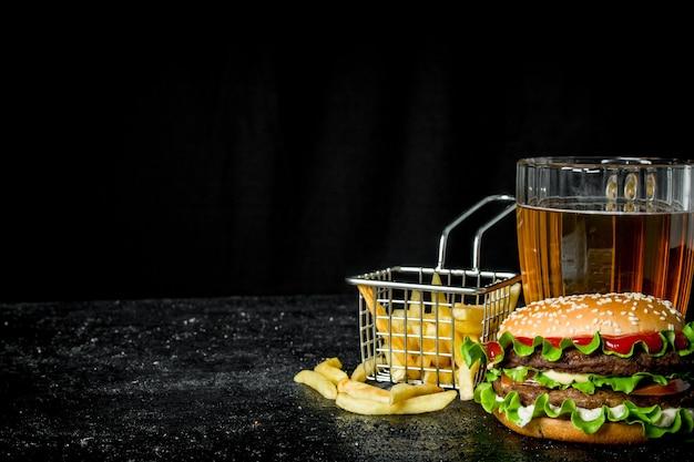 Hamburger met frietjes en bier op rustieke tafel.