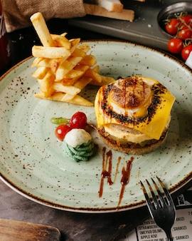 Hamburger met frietjes en tomaten op plaat